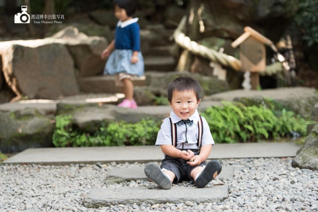 境内の石の上に座る男の子