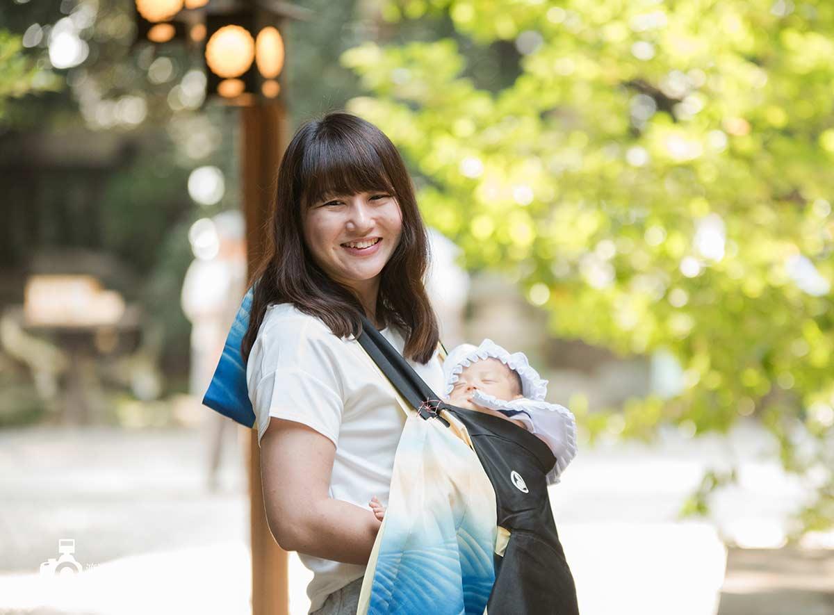 お宮参りで女性が赤ちゃんを抱いて笑っている