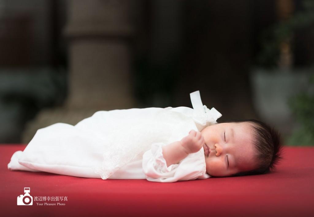 赤い縁台の上に横になり寝る赤ちゃん