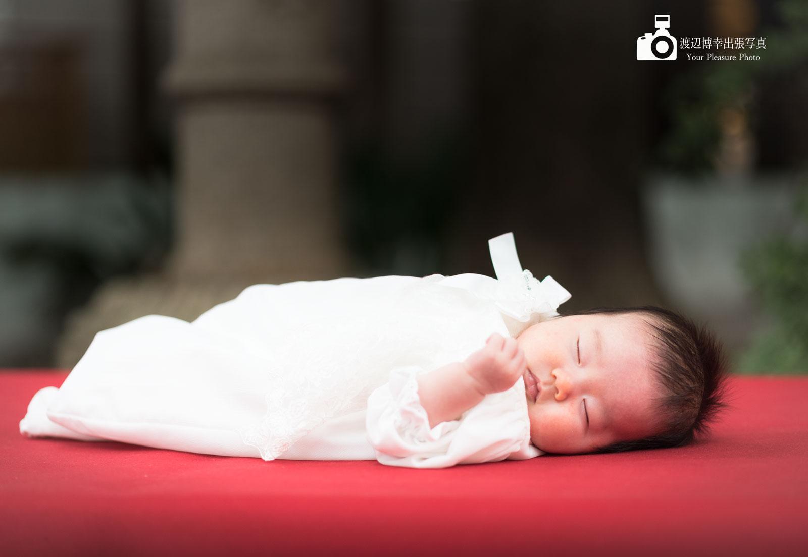 赤い縁台の上で寝ている赤ちゃん