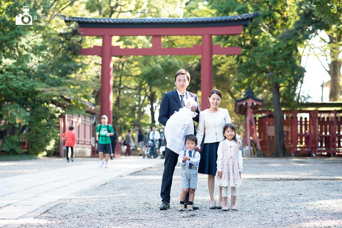 大宮氷川神社の鳥居の前でポーズを取っている家族