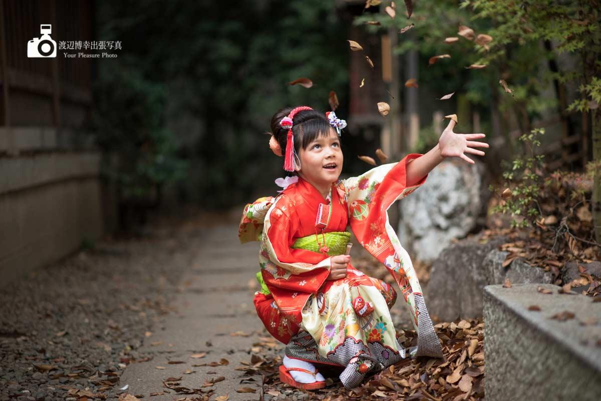 着物を着ているしゃがんだ女の子が葉っぱを投げている