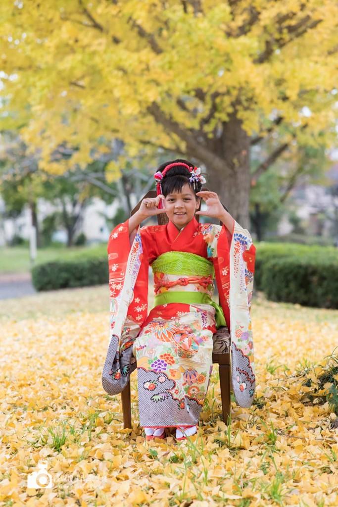 イチョウの木の下でカメラのポーズを取る椅子に座る女の子