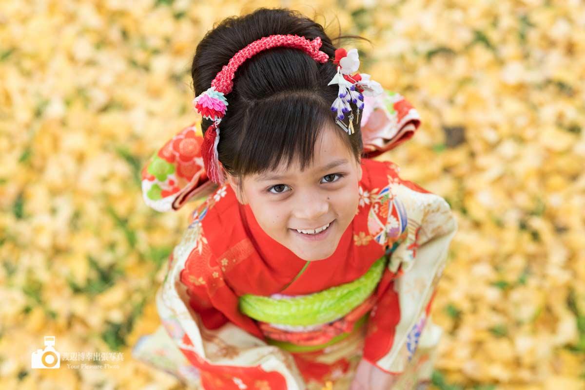 イチョウの葉っぱの上で上を見上げる着物姿の女の子