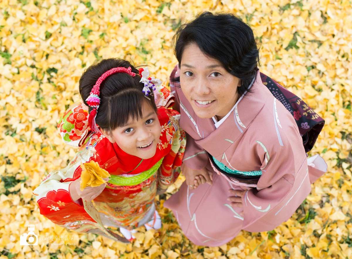 イチョウの葉っぱの上で上を見上げる着物姿のママと女の子