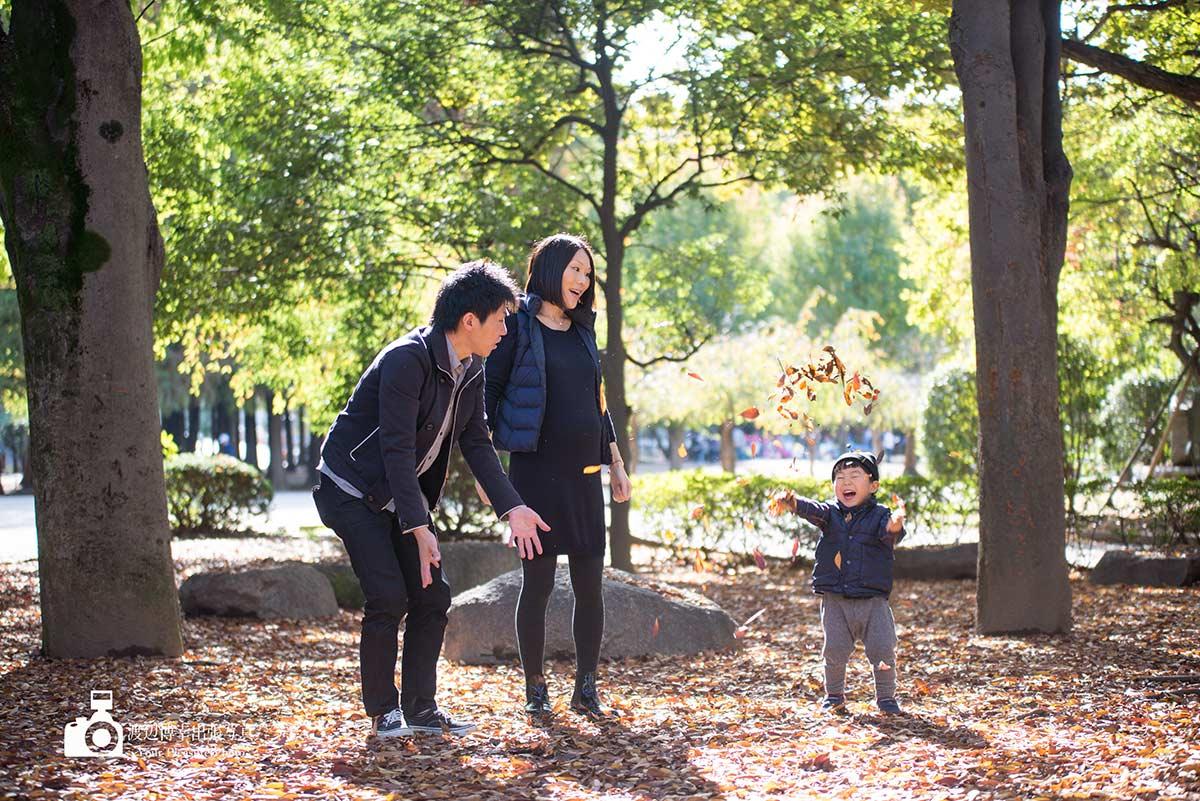 3人家族の中の男の子が葉っぱで遊んでいる