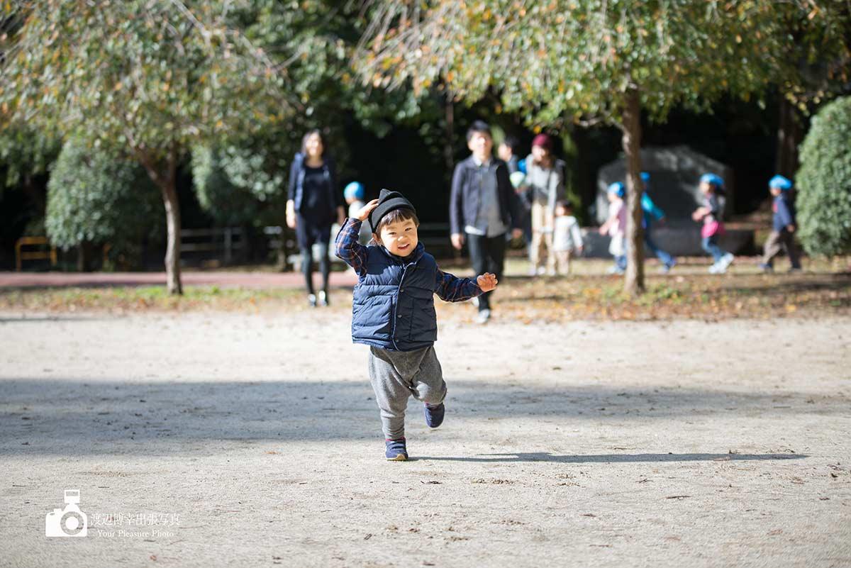 男の子が家族に見守られて走ってくる写真