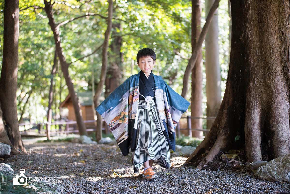七五三の男の子が木の下を歩いている