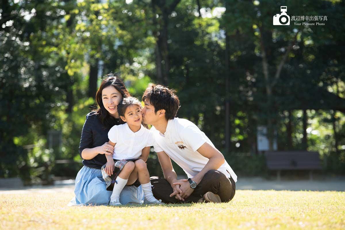 パパが女の子にキスをしている3人家族