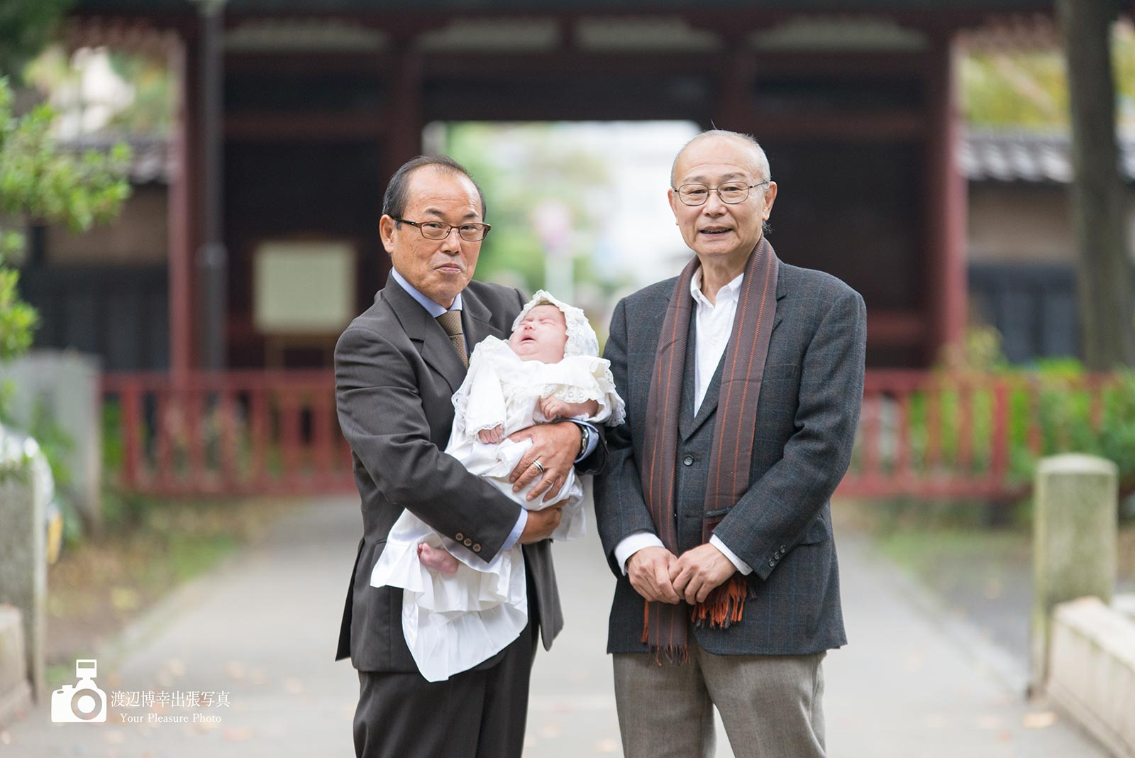 お宮参りで赤ちゃんを抱く二人の祖父