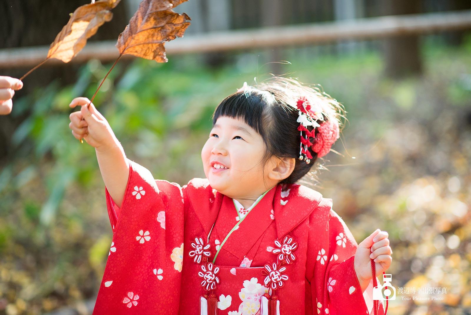 葉っぱで遊んでいる赤い着物を着た女の子