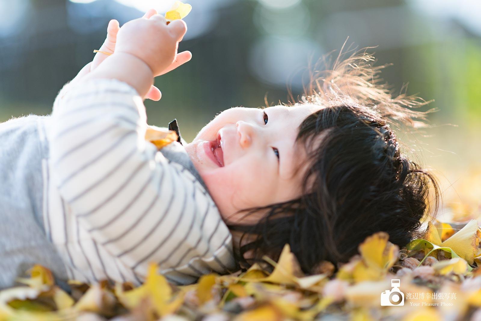 笑っているイチョウの上の赤ちゃん