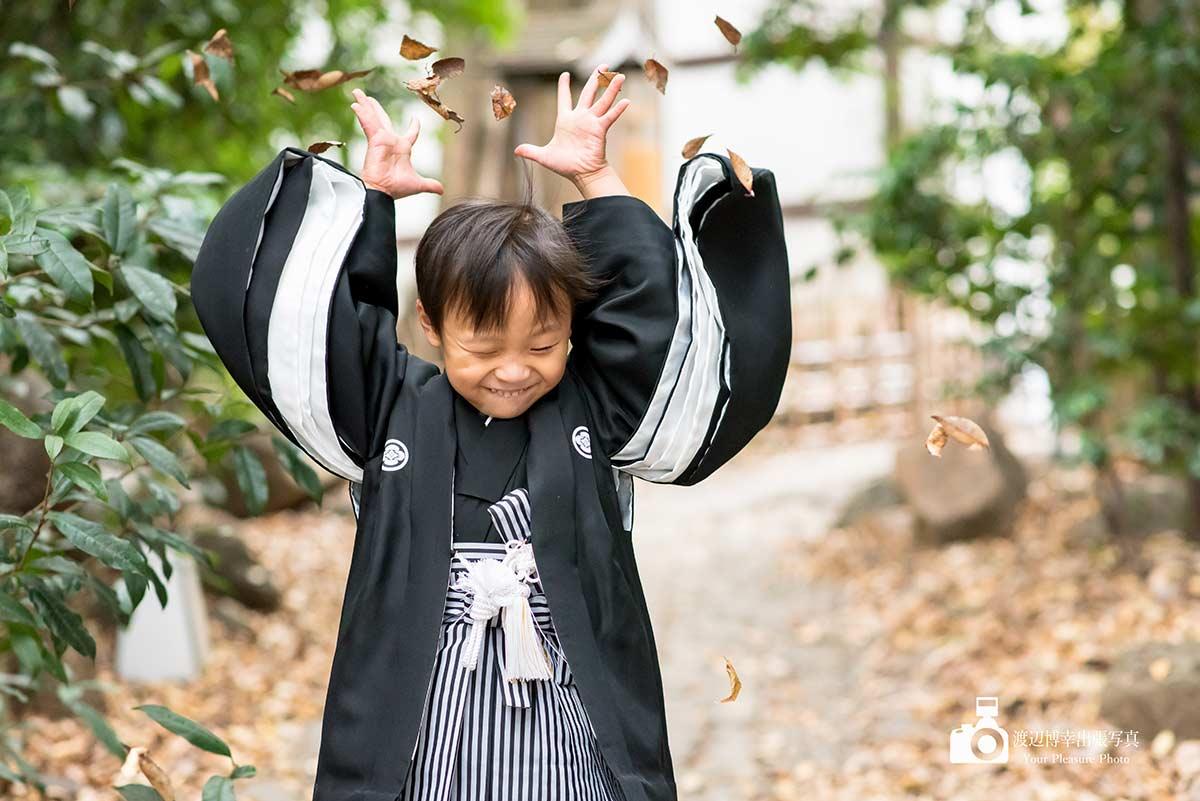 葉っぱで遊んでいる着物姿の男の子