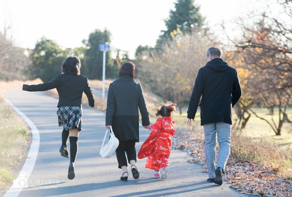 土手を歩く4人家族の後ろ姿