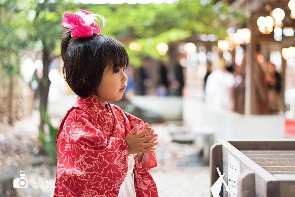 手を合わせてお祈りする七五三の着物姿の女の子