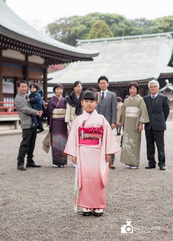753の記念写真で家族の前に着物姿で立つ女の子