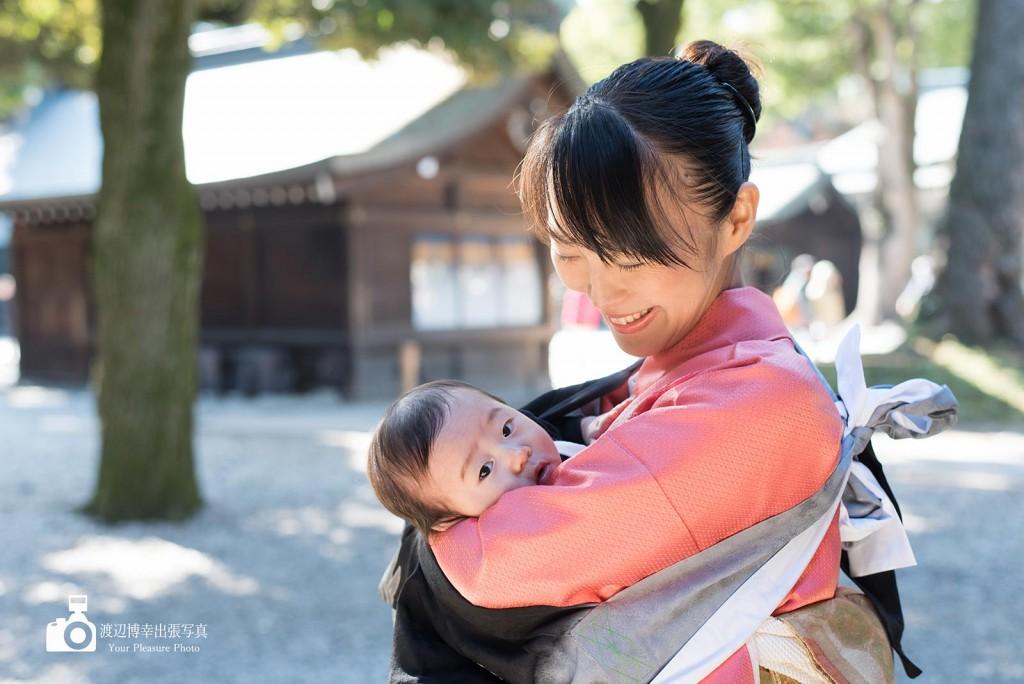 ピンクの和服姿の母に抱かれたお宮参りの赤ちゃん