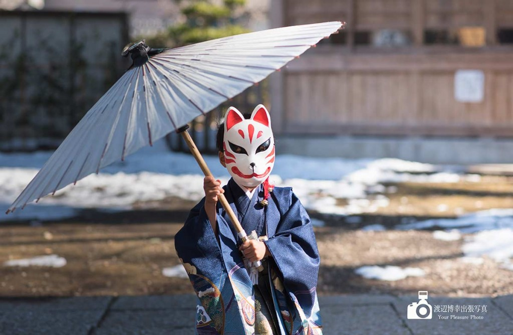狐のお面を被って番傘を指す七五三の男の子