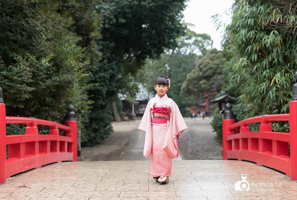 赤い橋の上に1人で立つ着物姿の女の子