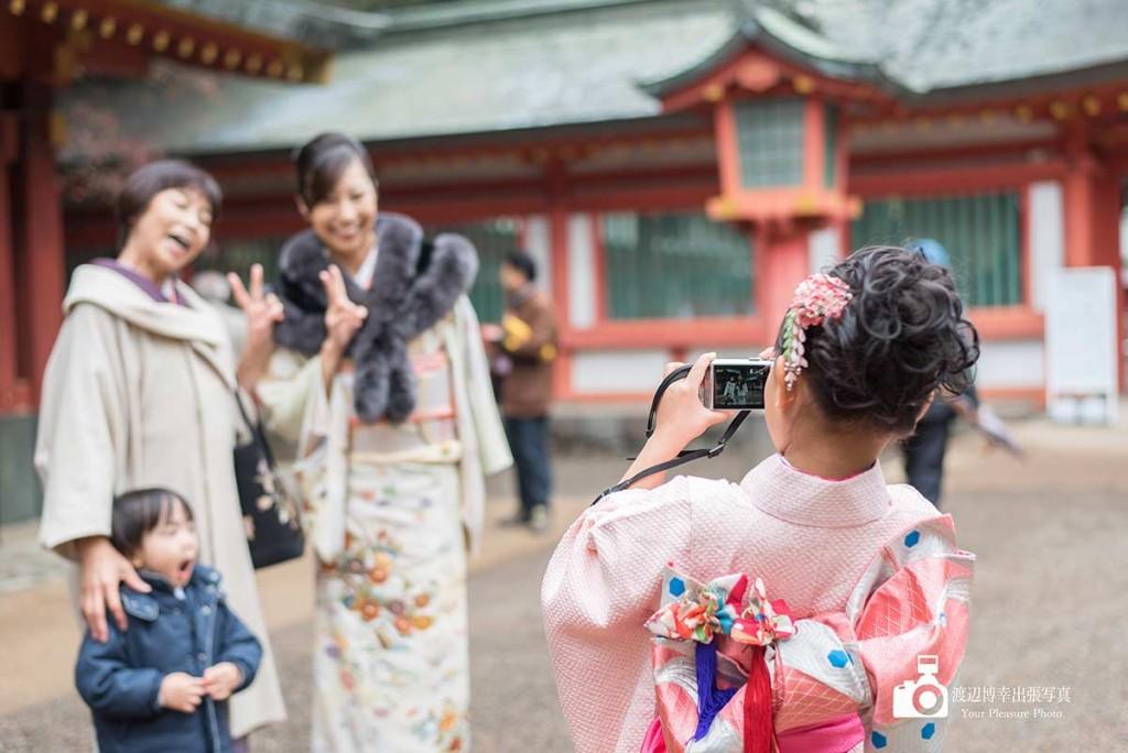カメラで写真を撮る着物姿の女の子