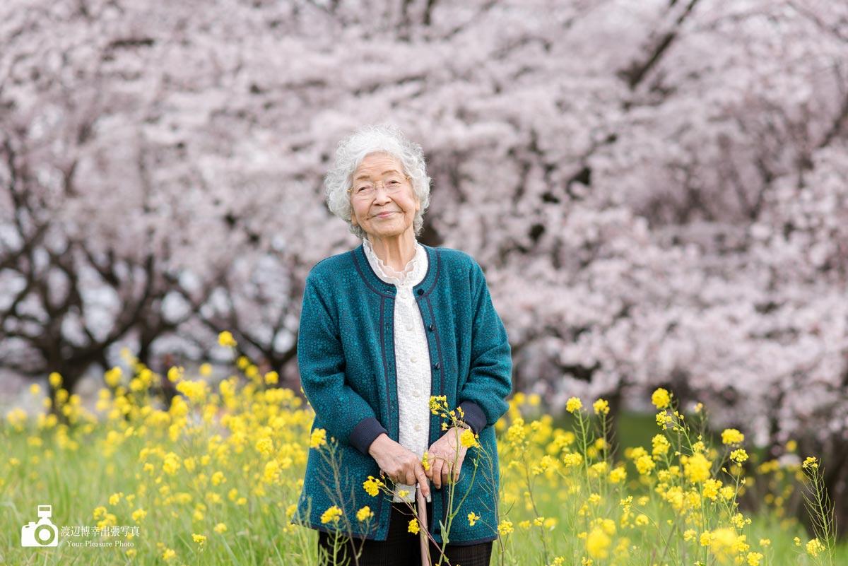 桜と菜の花がバックのおばあちゃん