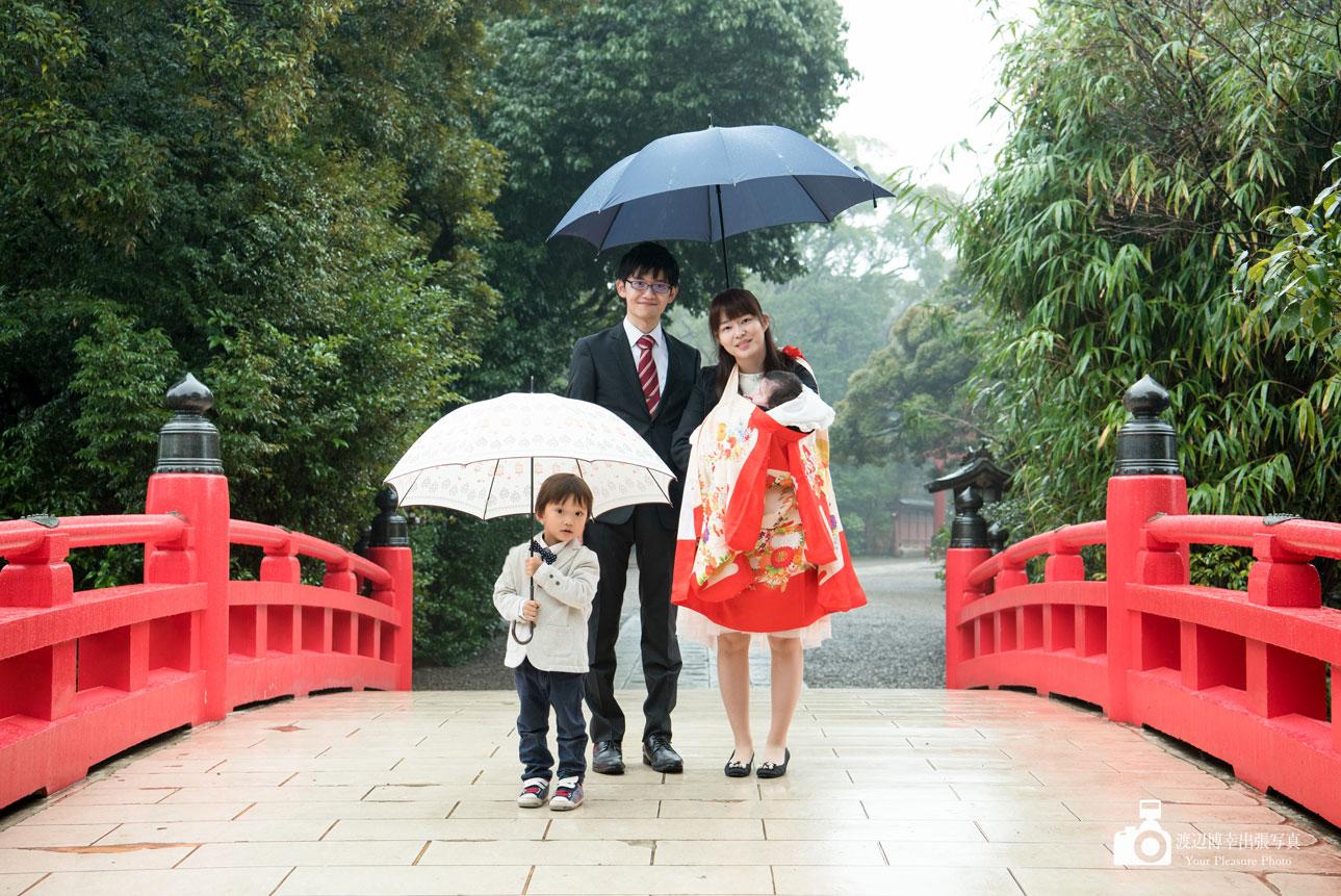 赤い橋の上に立つお宮参りの家族
