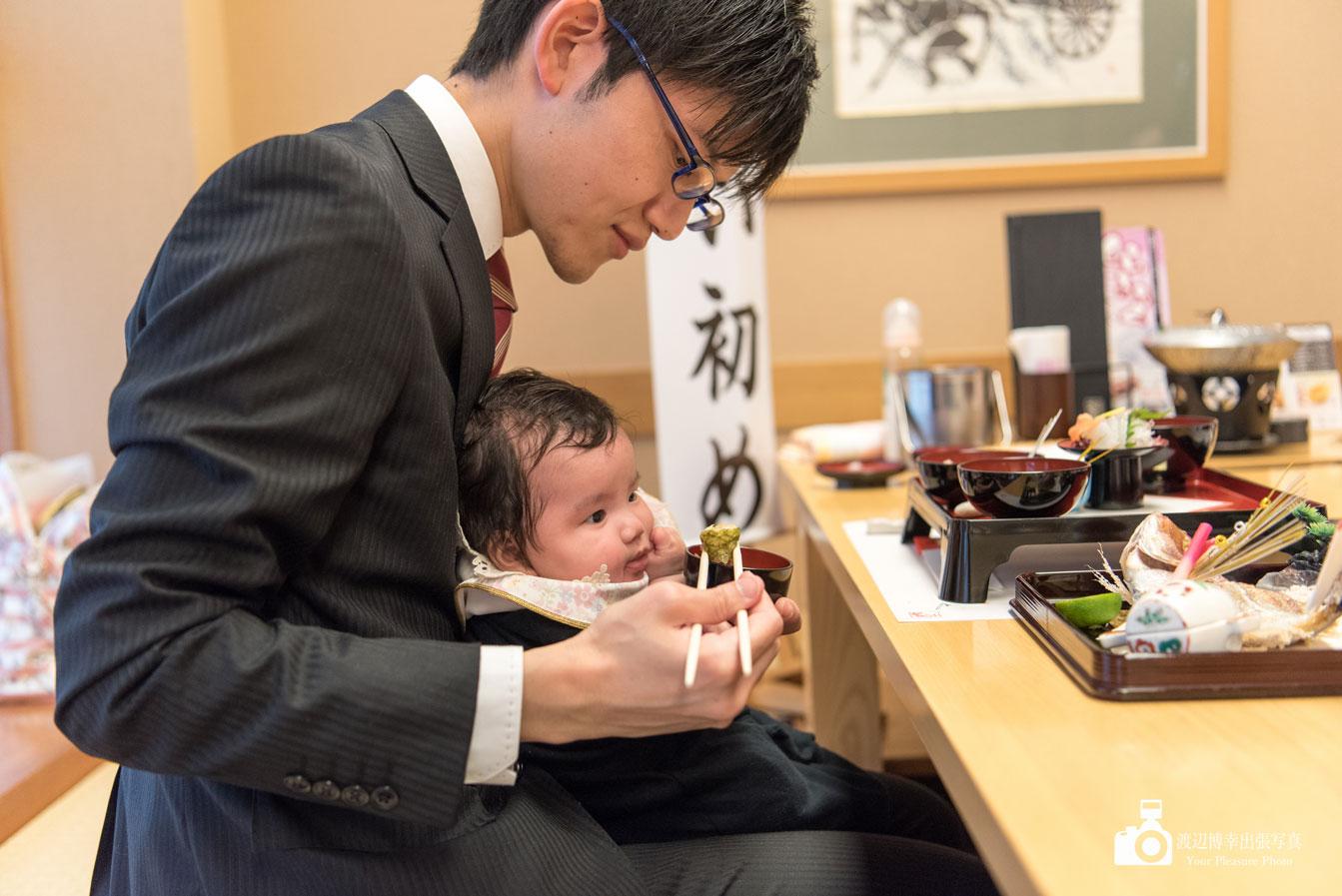 赤ちゃんにお食い初めの食事をさせるお父さん