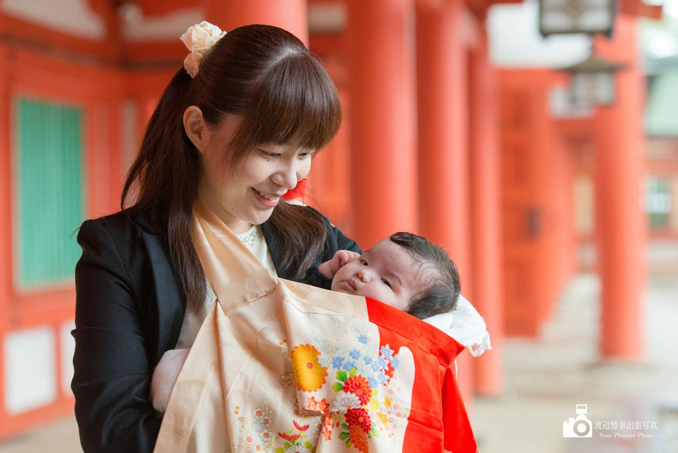 神社の赤い柱の下の女性と赤ちゃん