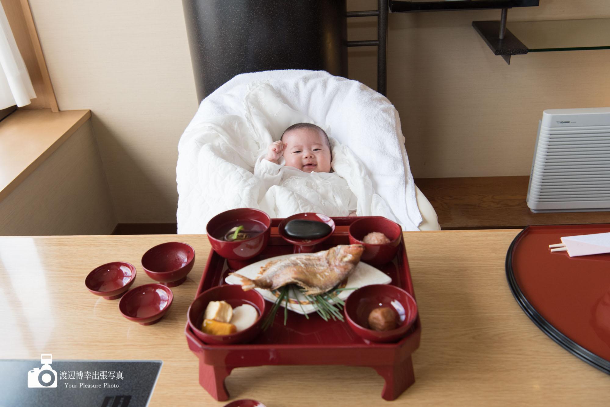 お食い初め膳を前にして笑う赤ちゃん