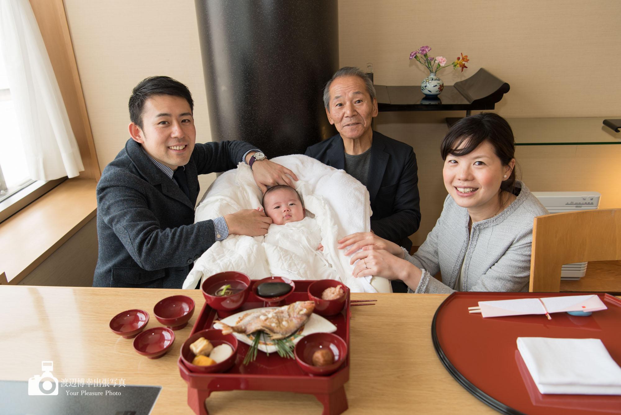 お食い初めの赤ちゃんを囲んで写真