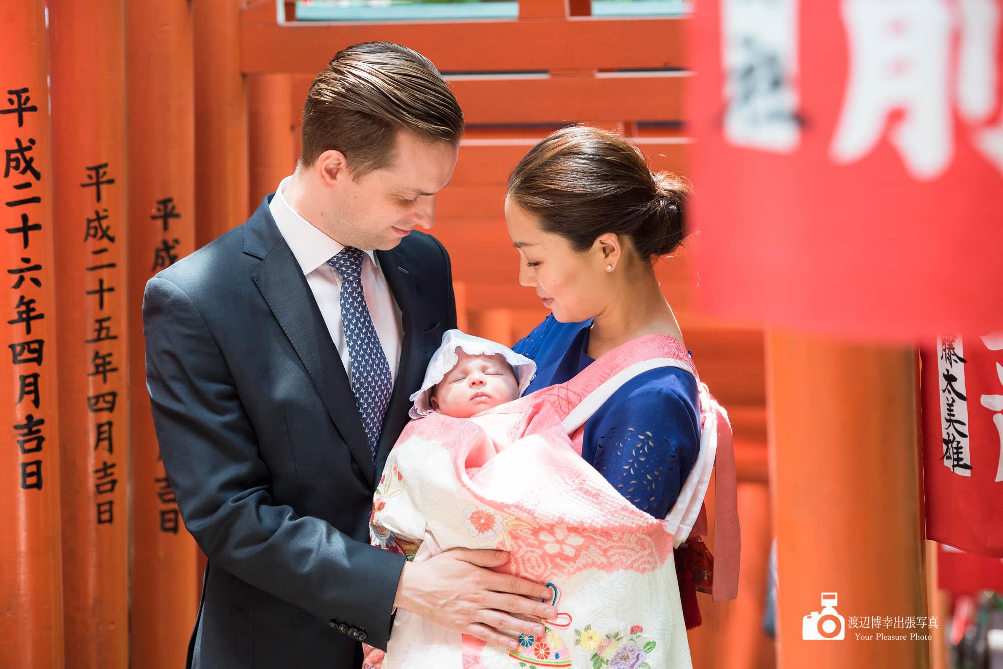 連続する鳥居の下で赤ちゃんを抱く夫婦