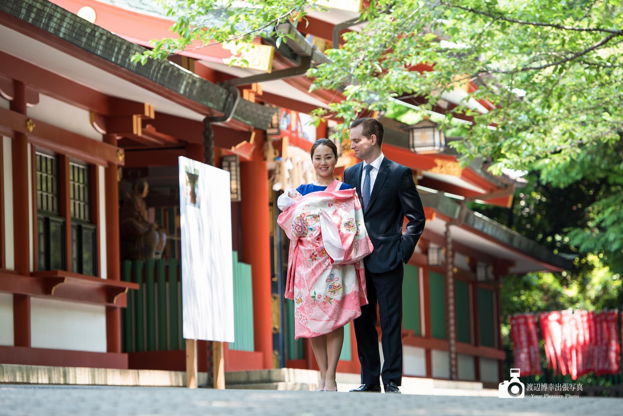 赤坂日枝神社の前で赤ちゃんを抱き並ぶお宮参りの夫婦