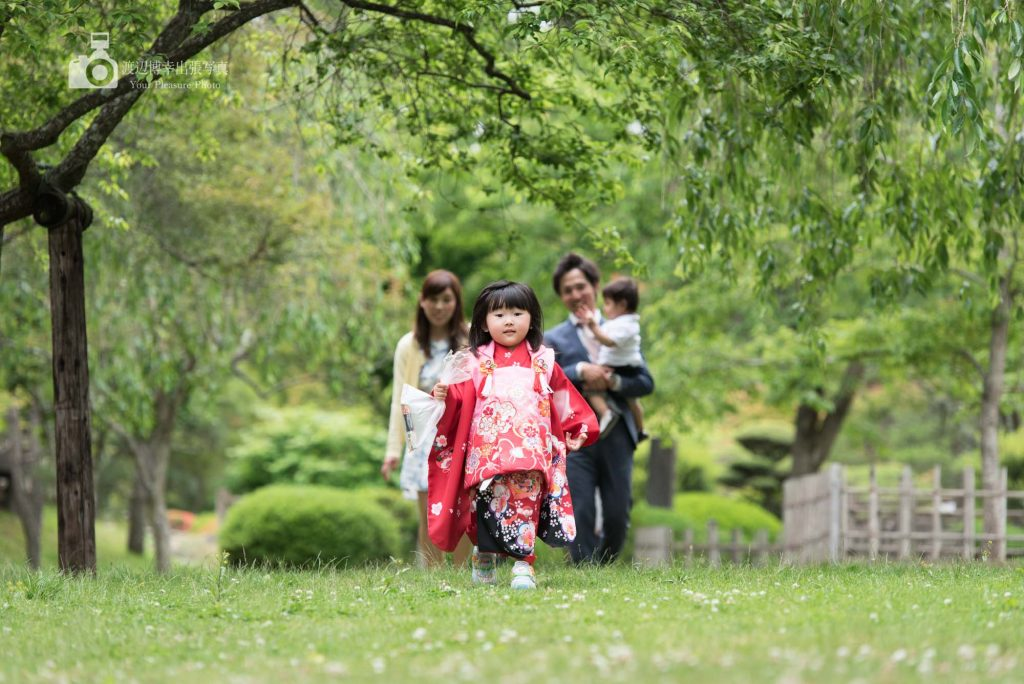 赤い着物で芝生の上を歩く七五三の女の子