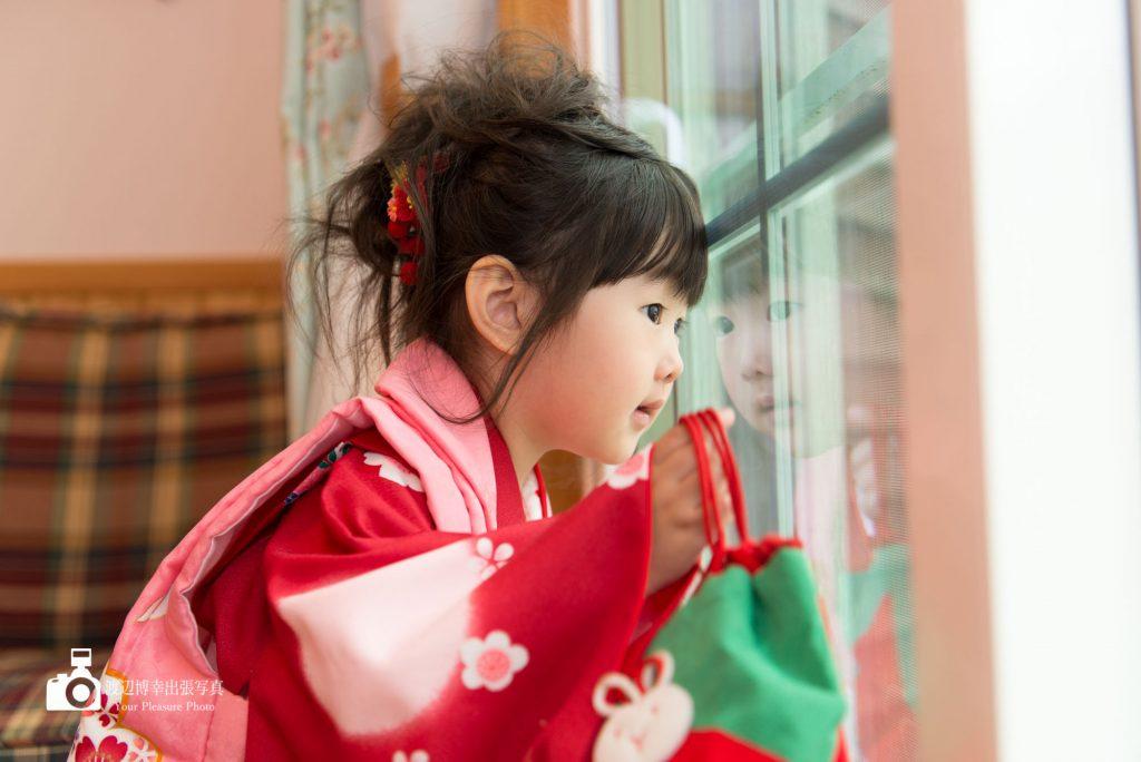赤い着物姿で窓の外を見ている七五三の女の子