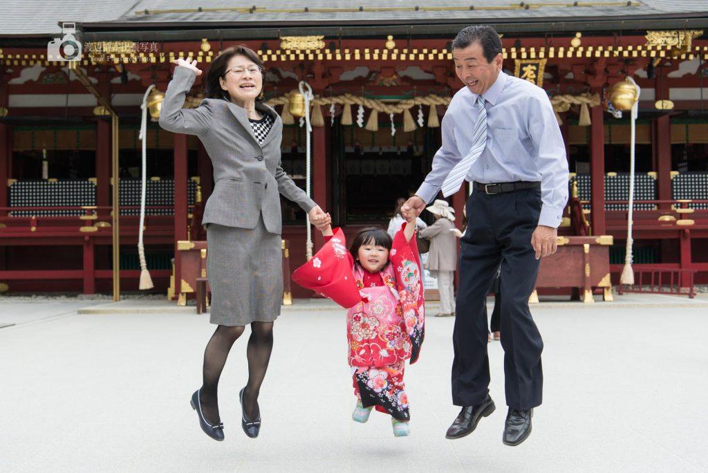 おじいちゃんおばあちゃんと神社でジャンプする赤い着物の女の子