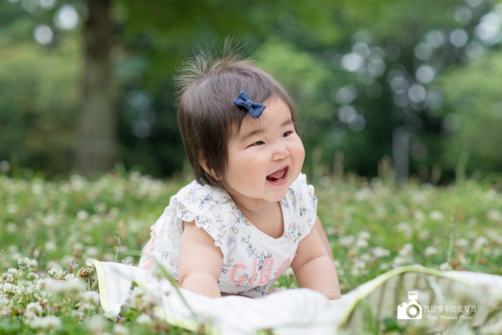 シロツメグサの上でハイハイをする笑顔の赤ちゃん
