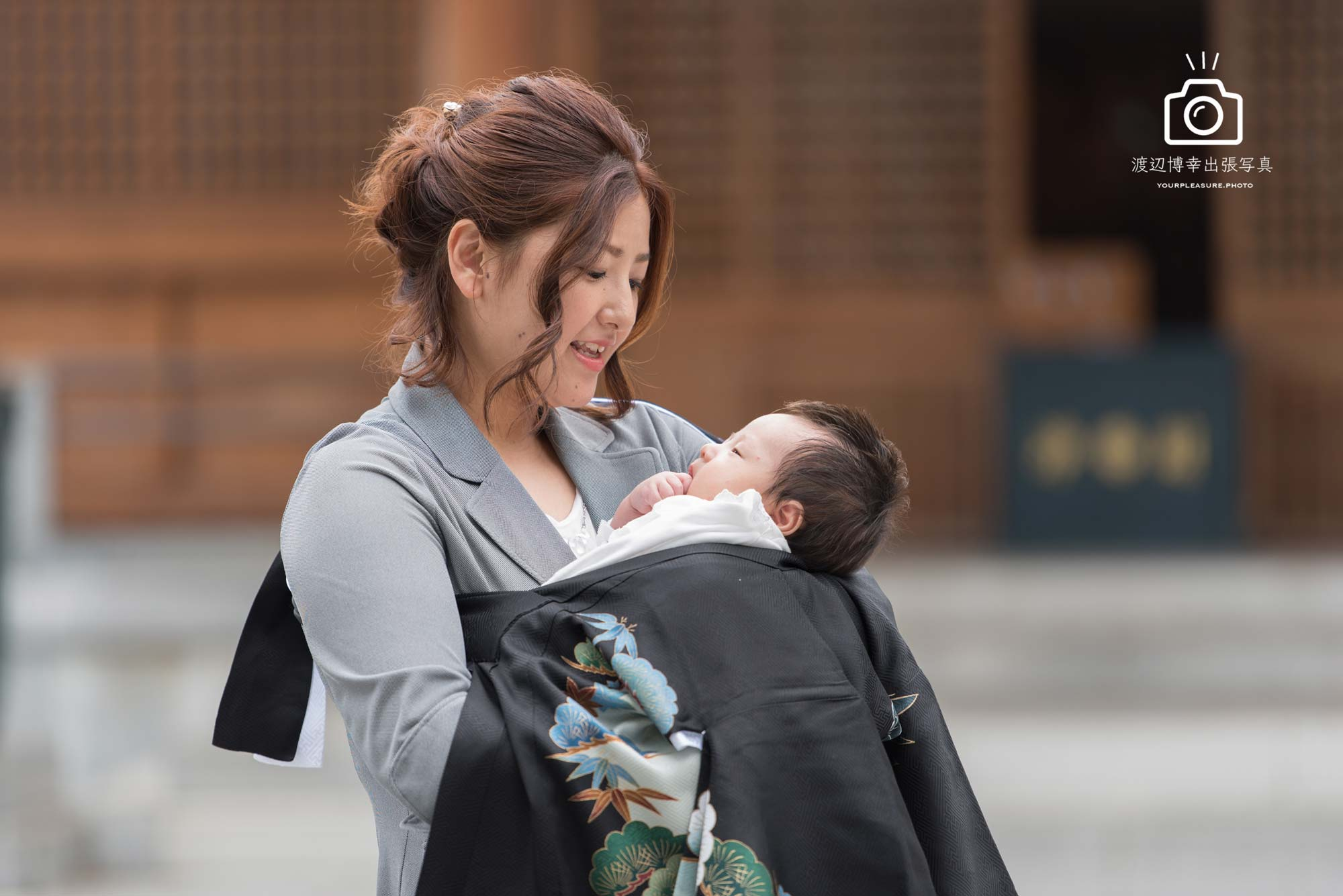お宮参りで赤ちゃんを抱くママ