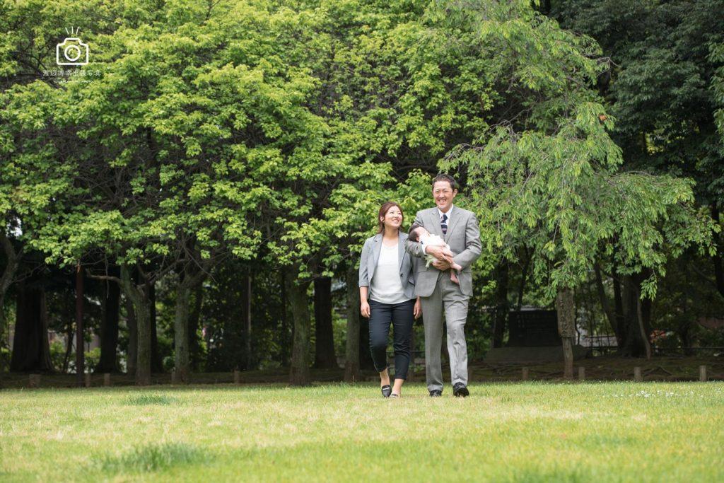 芝生の上で赤ちゃんを抱く夫婦