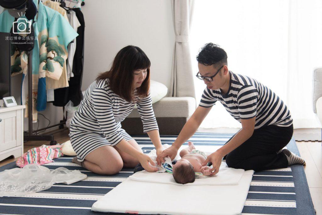 部屋の中で赤ちゃんのおしめを取り替える夫婦