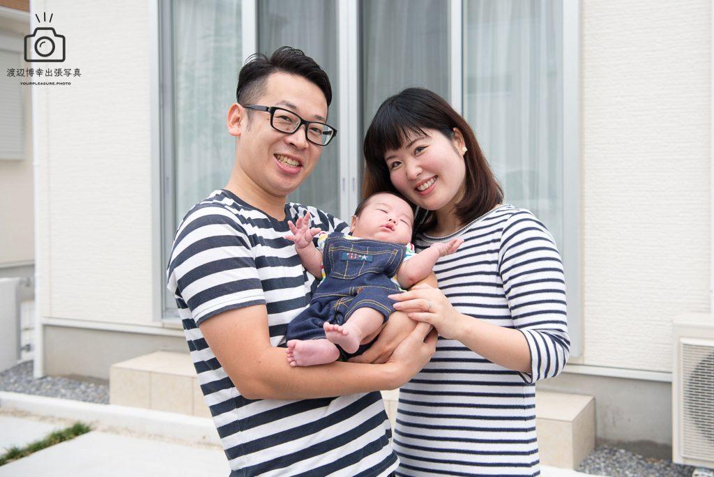 自宅前で赤ちゃんと記念写真を撮る若い夫婦