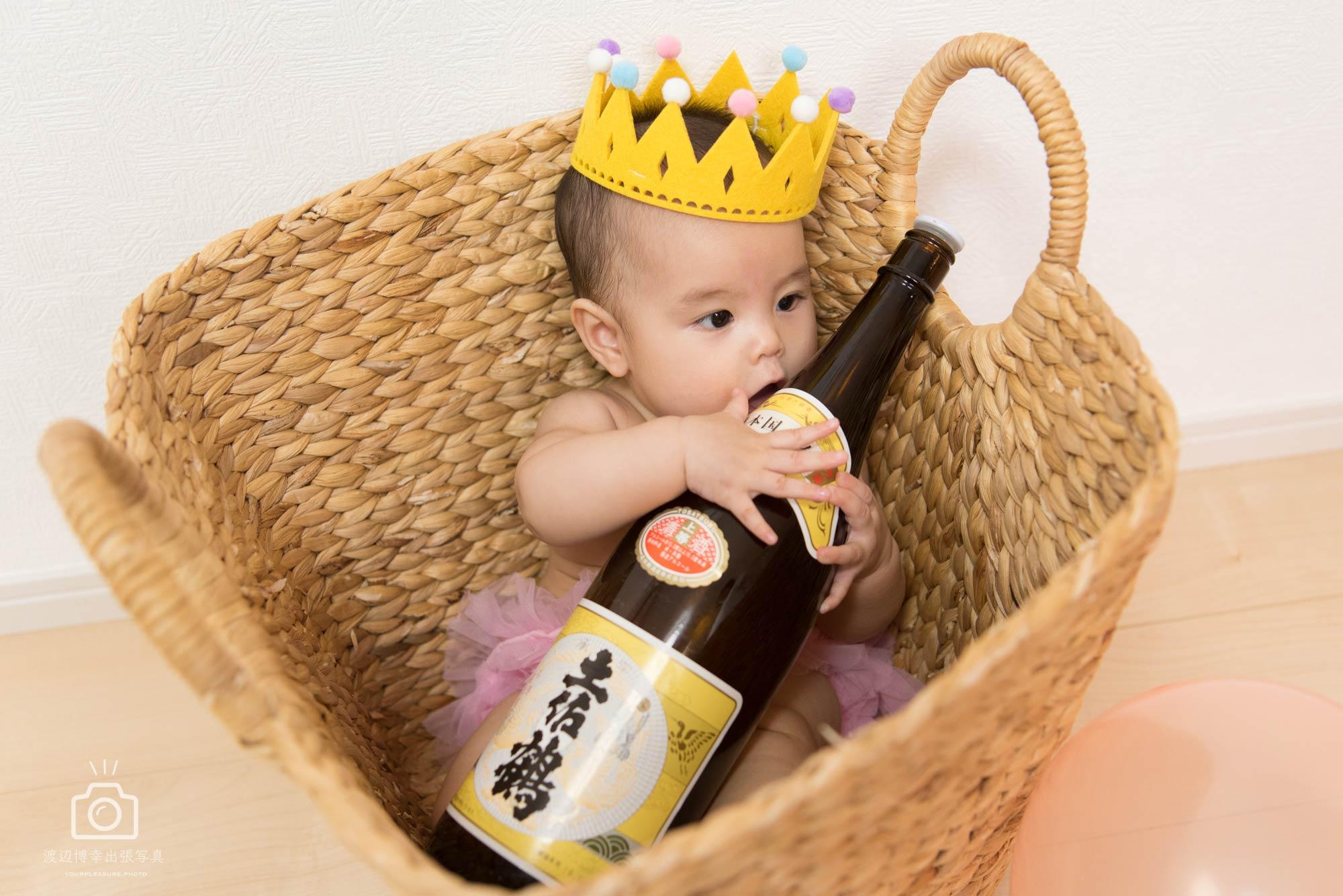 日本酒の瓶を抱えている赤ちゃん