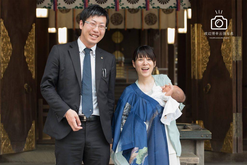 神社の本殿の前で笑っているお宮参りのパパとママ