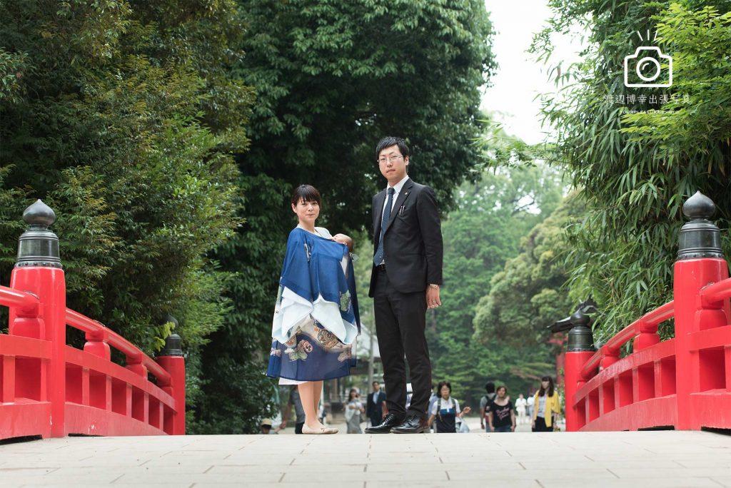 お宮参りのパパとママが赤い橋の上に立っている