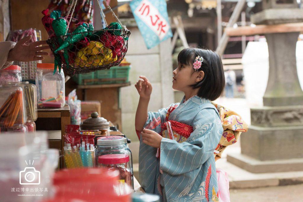 駄菓子屋で買い物をする七五三の女の子