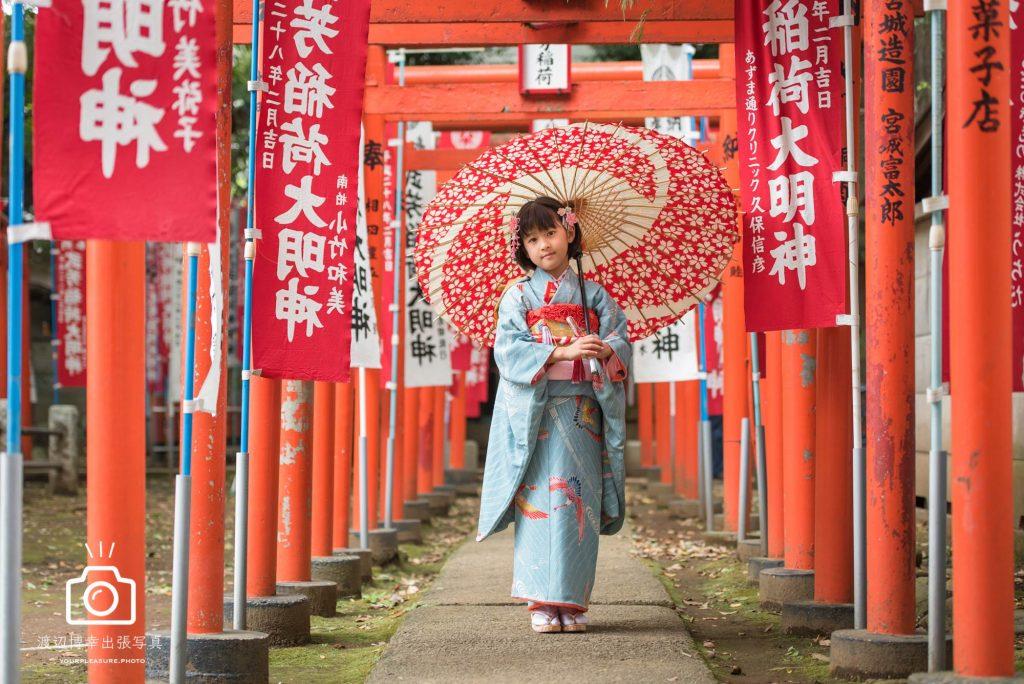 赤い鳥居の下で和傘を指す七五三の女の子