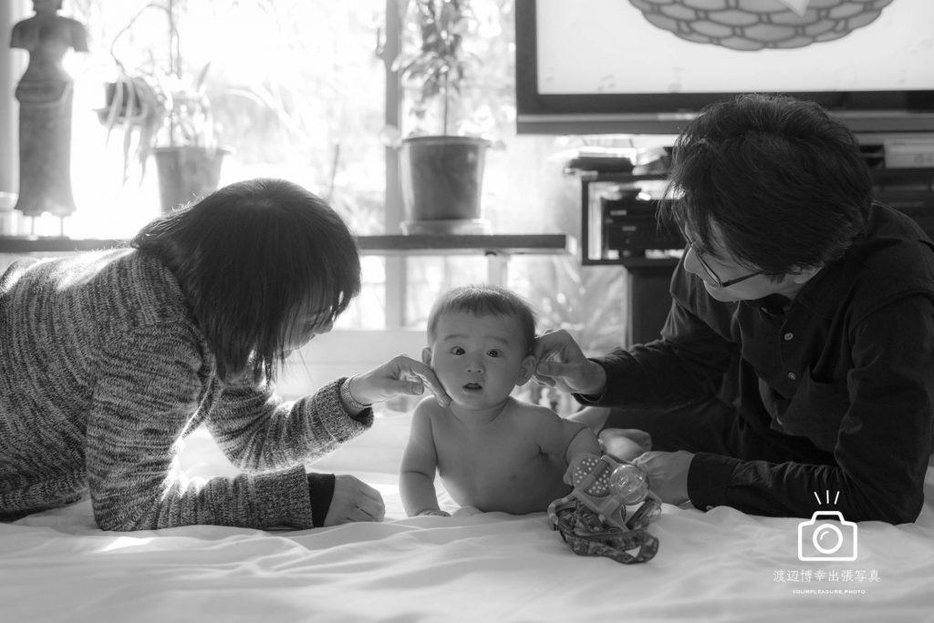 赤ちゃんとパパとママが床に寝転んでいる