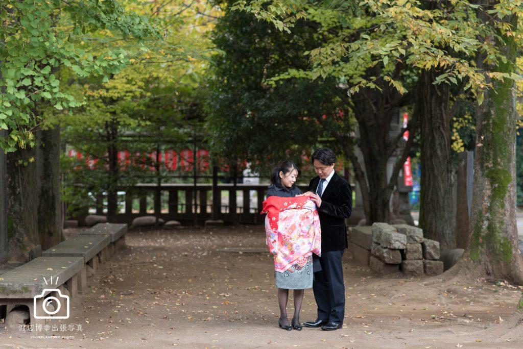 神社の林の中で赤ちゃんを抱くお宮参りの夫婦