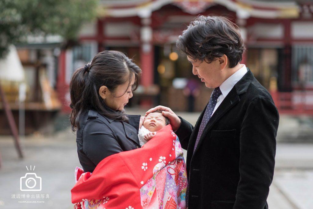 赤ちゃんの頭に手を置くお宮参りの夫婦