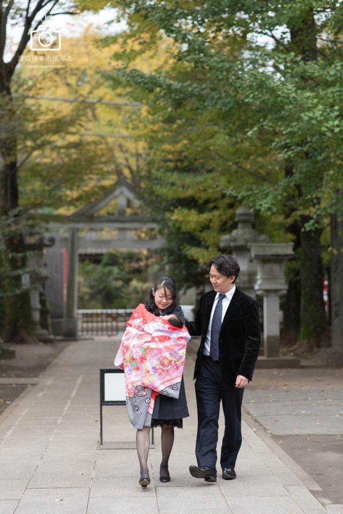 赤ちゃんをだいて歩くお宮参りの夫婦