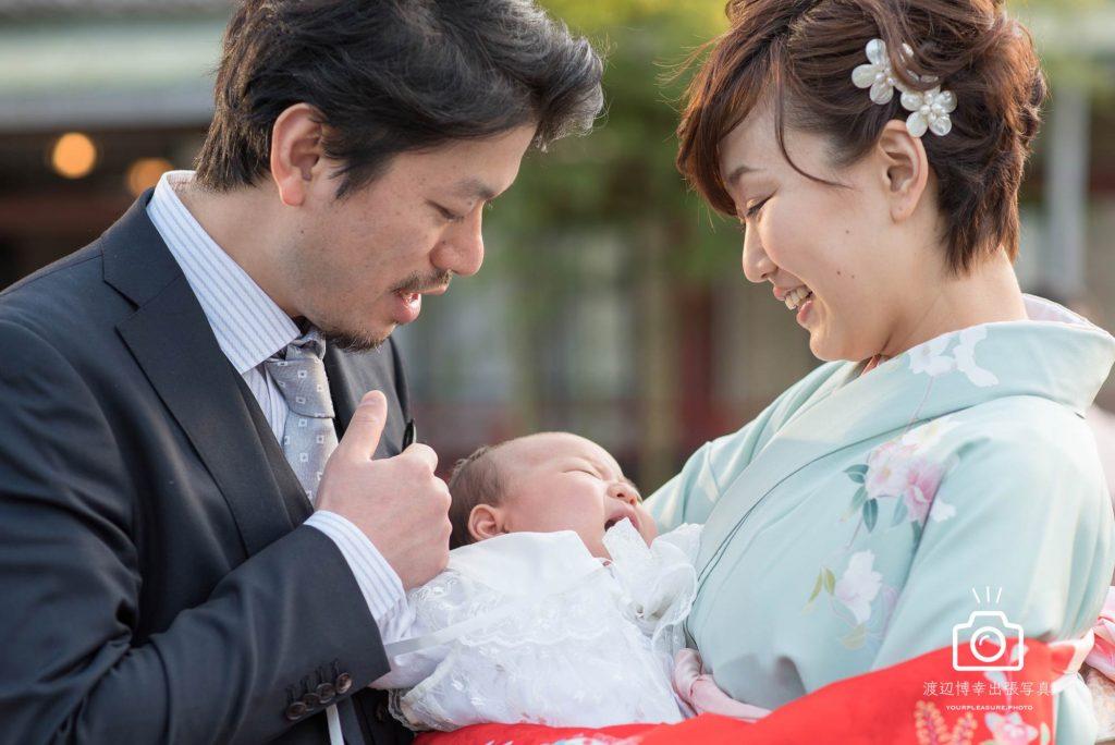 赤ちゃんを抱っこしたお宮参りの掛着を着た女性と横に立つ男性